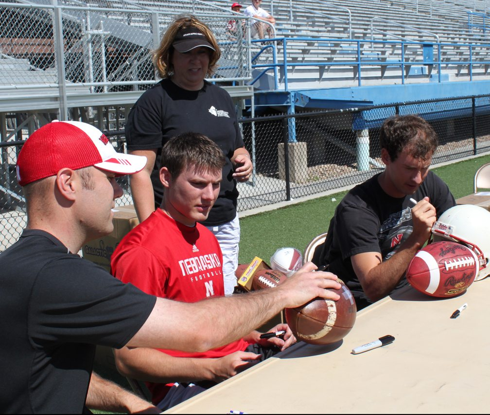 Kyle Larson, Brett Maher and Alex Henery sign autographs on footballs during the 2011 Kicker's Kick-Off