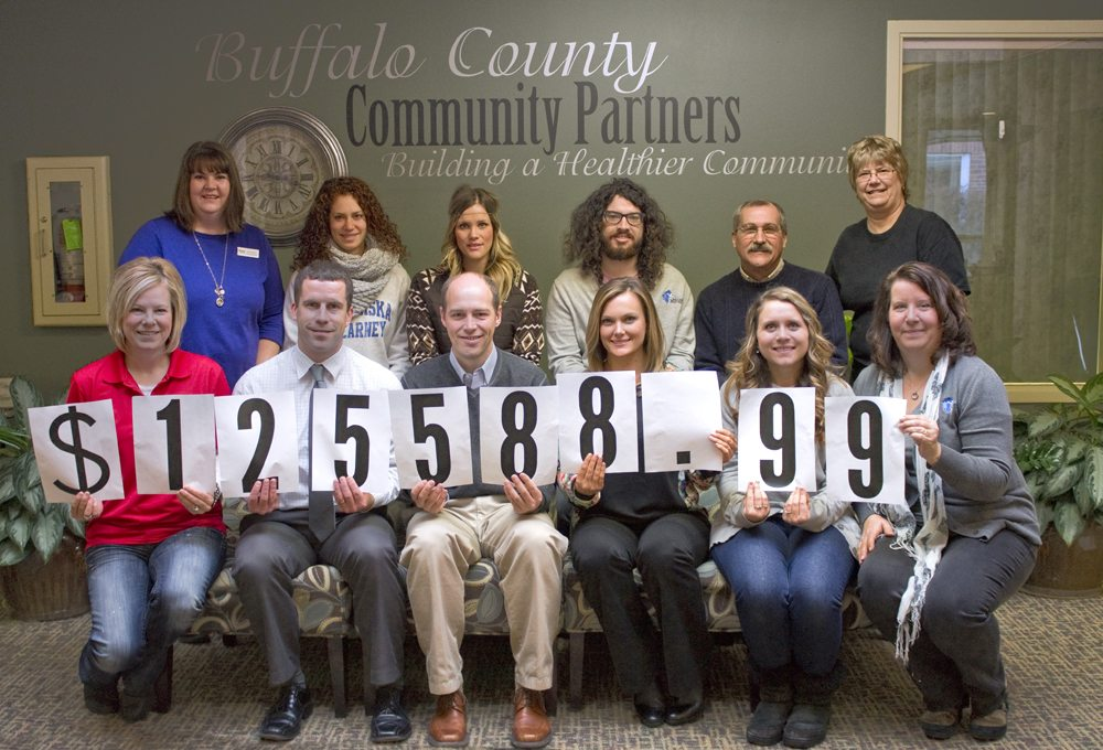 Community Partners' campaign committee and staff members show off the total amount raised in the 2014 annual fund campaign.