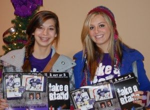 Isabel and Rosamond Thalken pose with the posters YAB created when they partnered with the Storm Hockey Team in 2009.